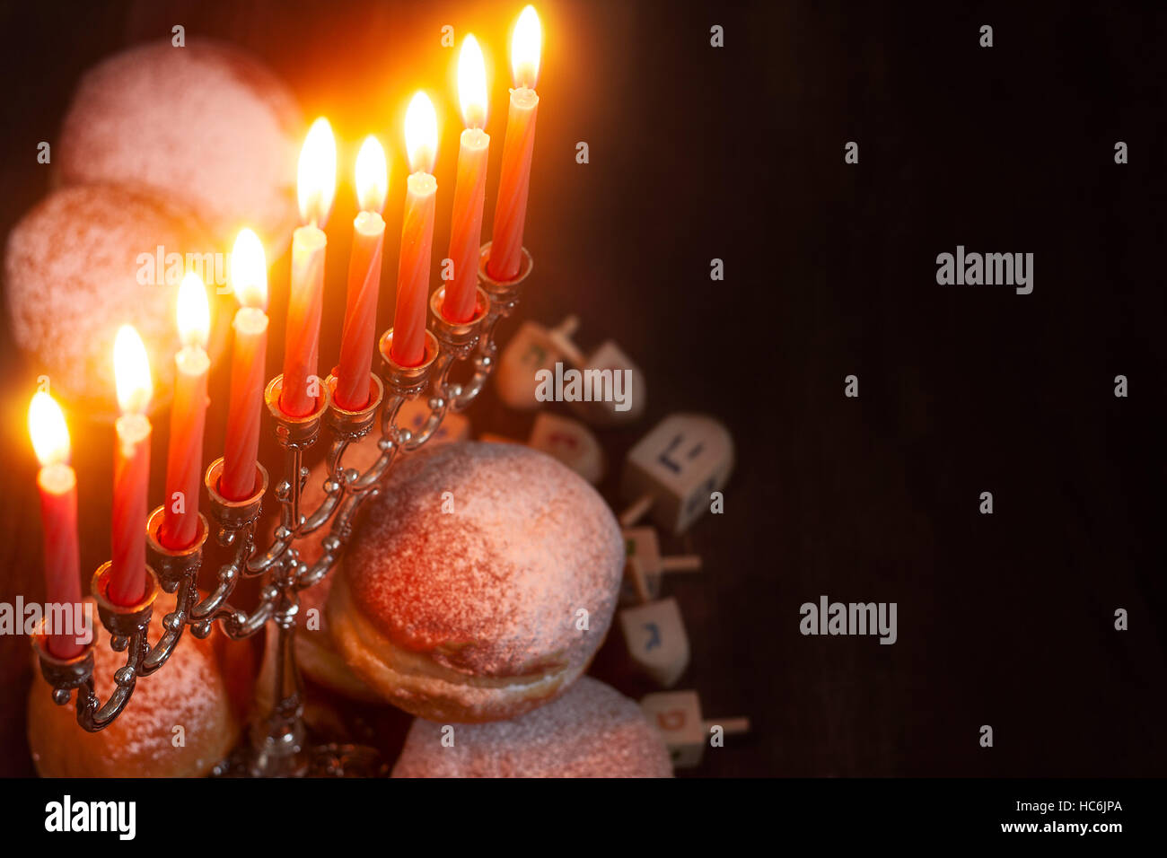 Symbols of jewish holiday hanukkah - menorah, donuts sufganiyot and dreidels - Stock Image