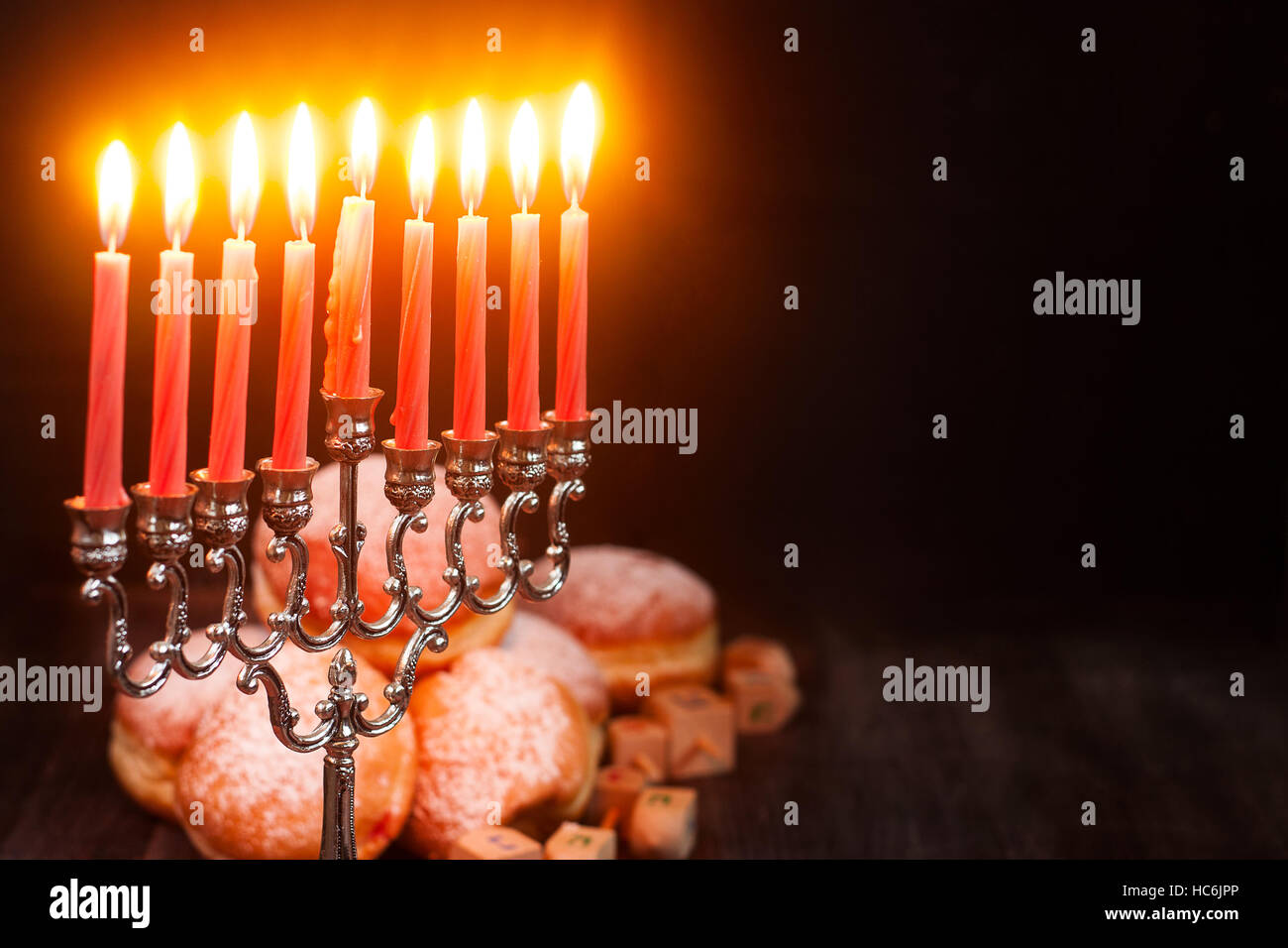 Symbols of jewish holiday hanukkah - menorah, donuts sufganiyot and dreidels - Stock Image
