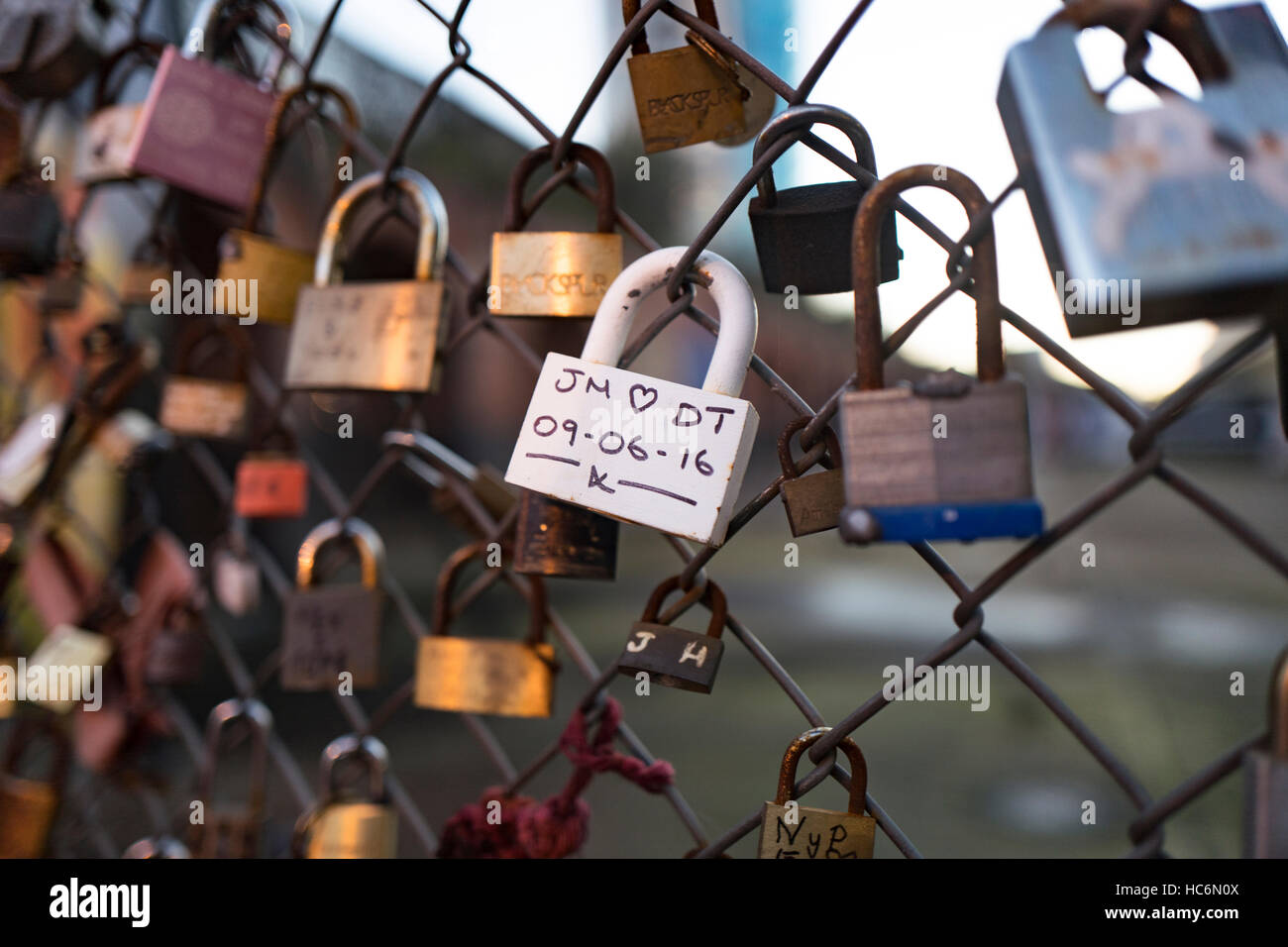 Love padlocks on wire fence outside Shoreditch High Street station Stock Photo
