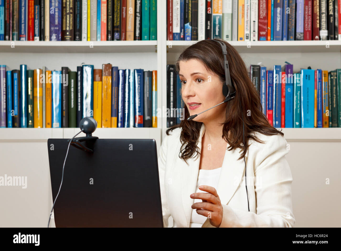 Teacher or tutor of a distance university giving an online lecture or tutorial in her office, mooc - Stock Image