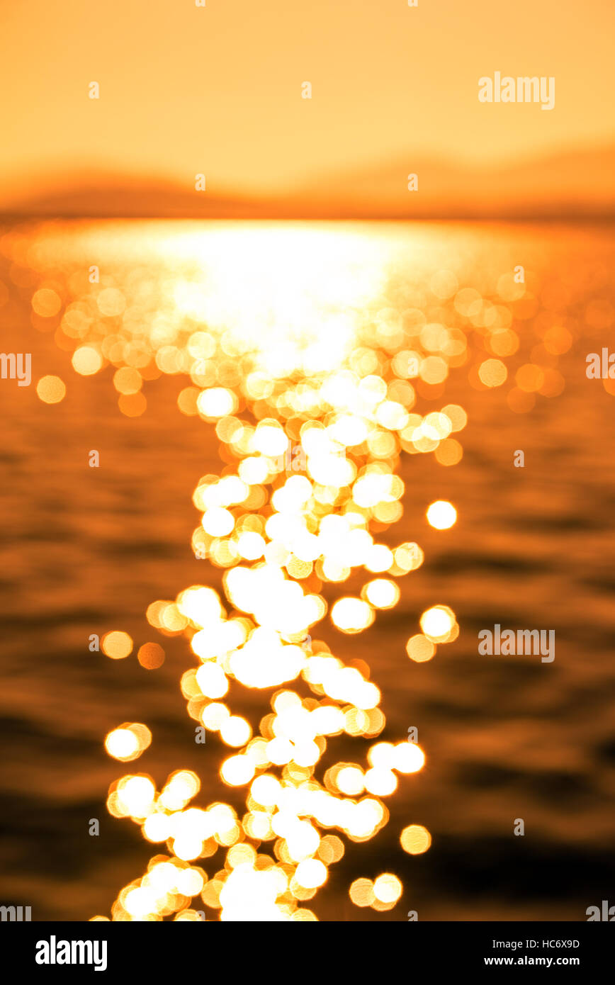 Blurred Image of  Beautiful Sun Reflection on Sea Waves at Sunset, Intentionally Out of Focus for Background use... - Stock Image