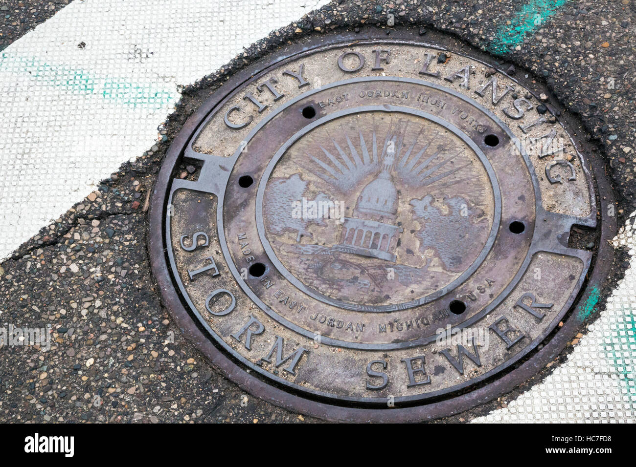 Lansing, Michigan - Storm sewer manhole covers in Michigan's capital city carry the image of the state's - Stock Image