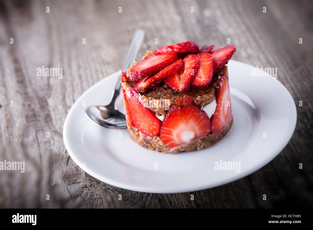 Strawberry and custard tart on a white plate . - Stock Image