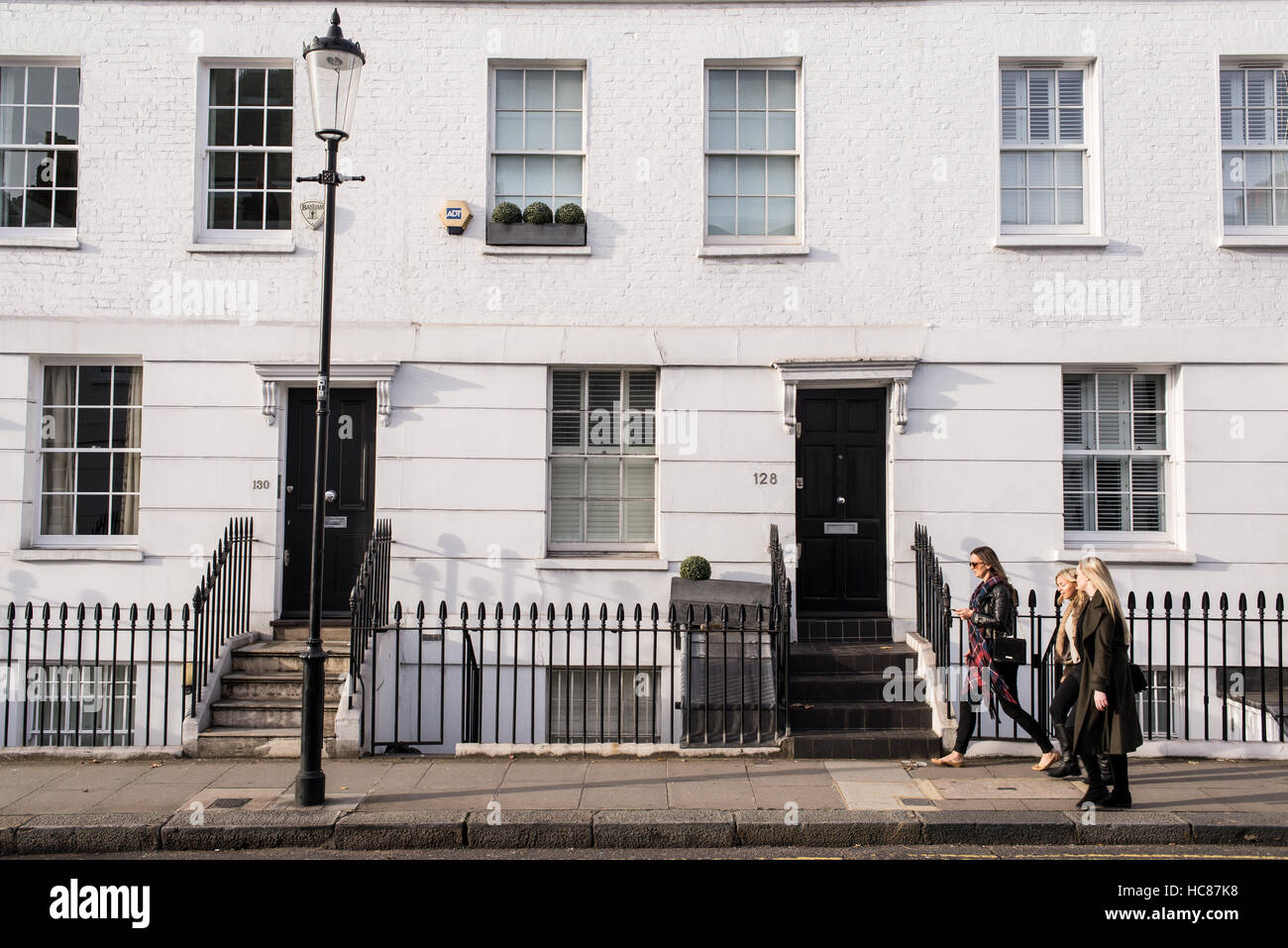 Three young women walking in a posh residential area of Chelsea, London, UK. Chelsea is an affluent area in southwest - Stock Image