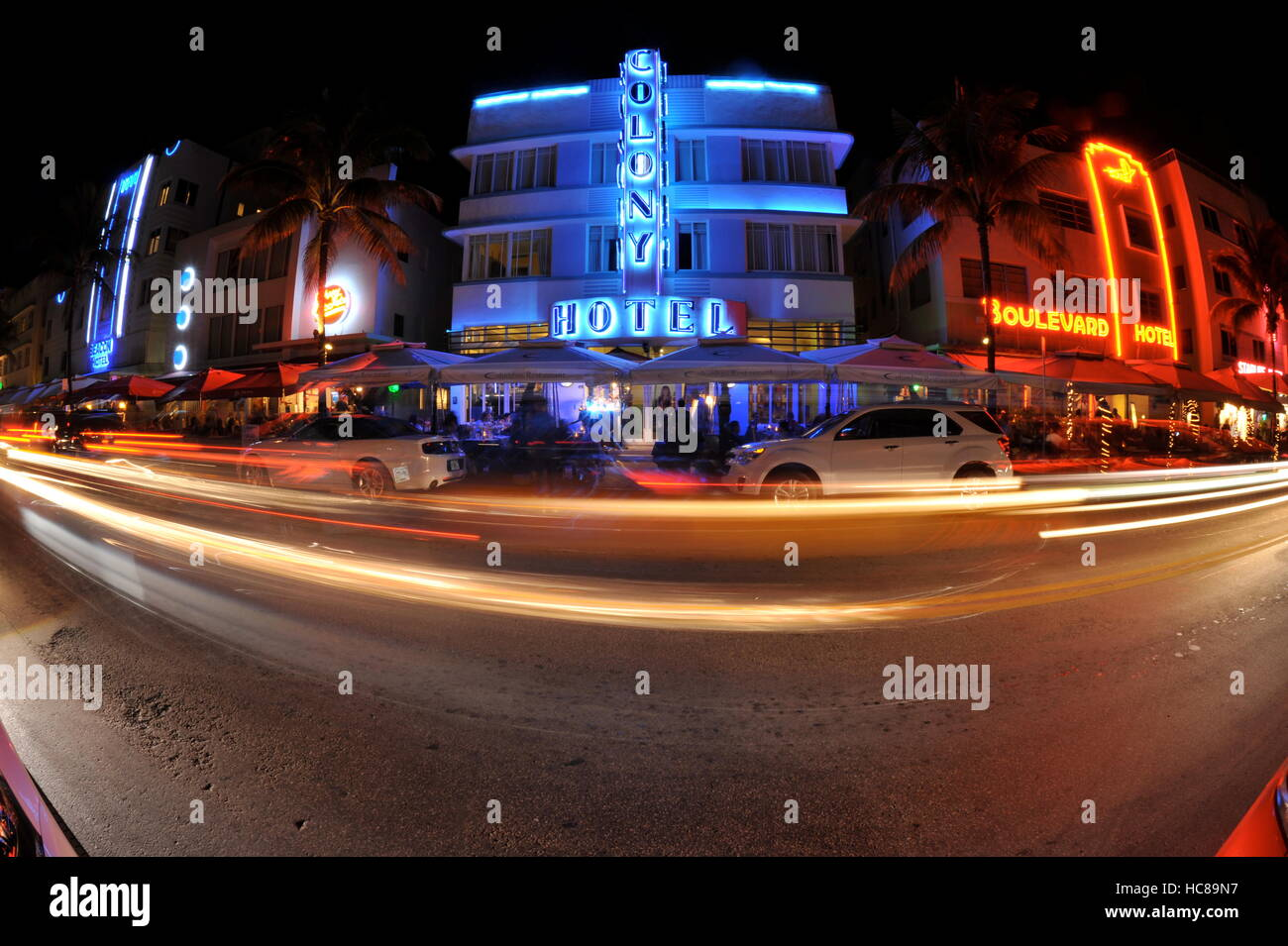 Row of art deco hotels at night with neon lights, including Colony Hotel, with vehicles blurring by with timed exposure, Stock Photo