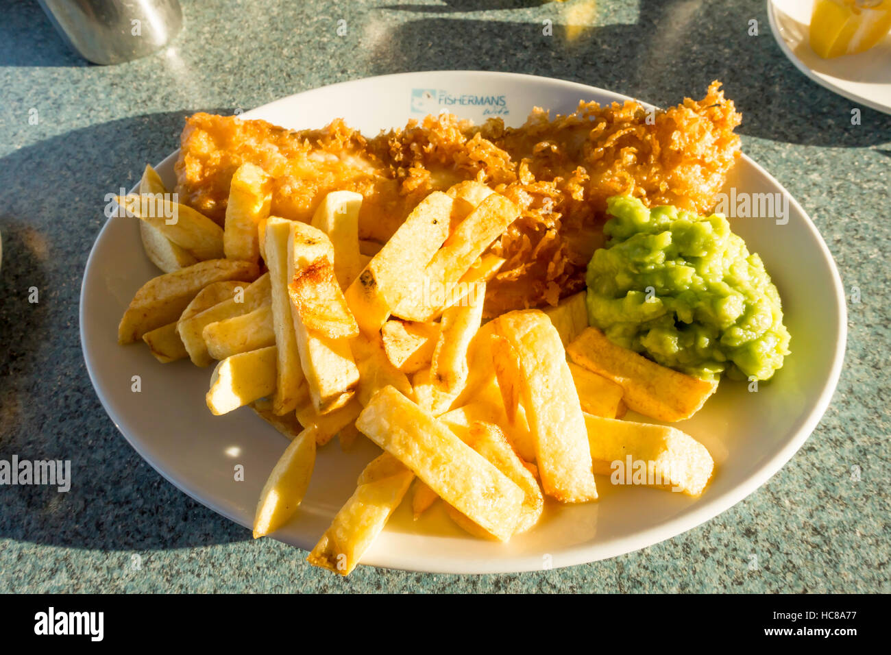 Excellent fish chips  and mushy peas at The Fishermans Wife Cafe in Whitby - Stock Image
