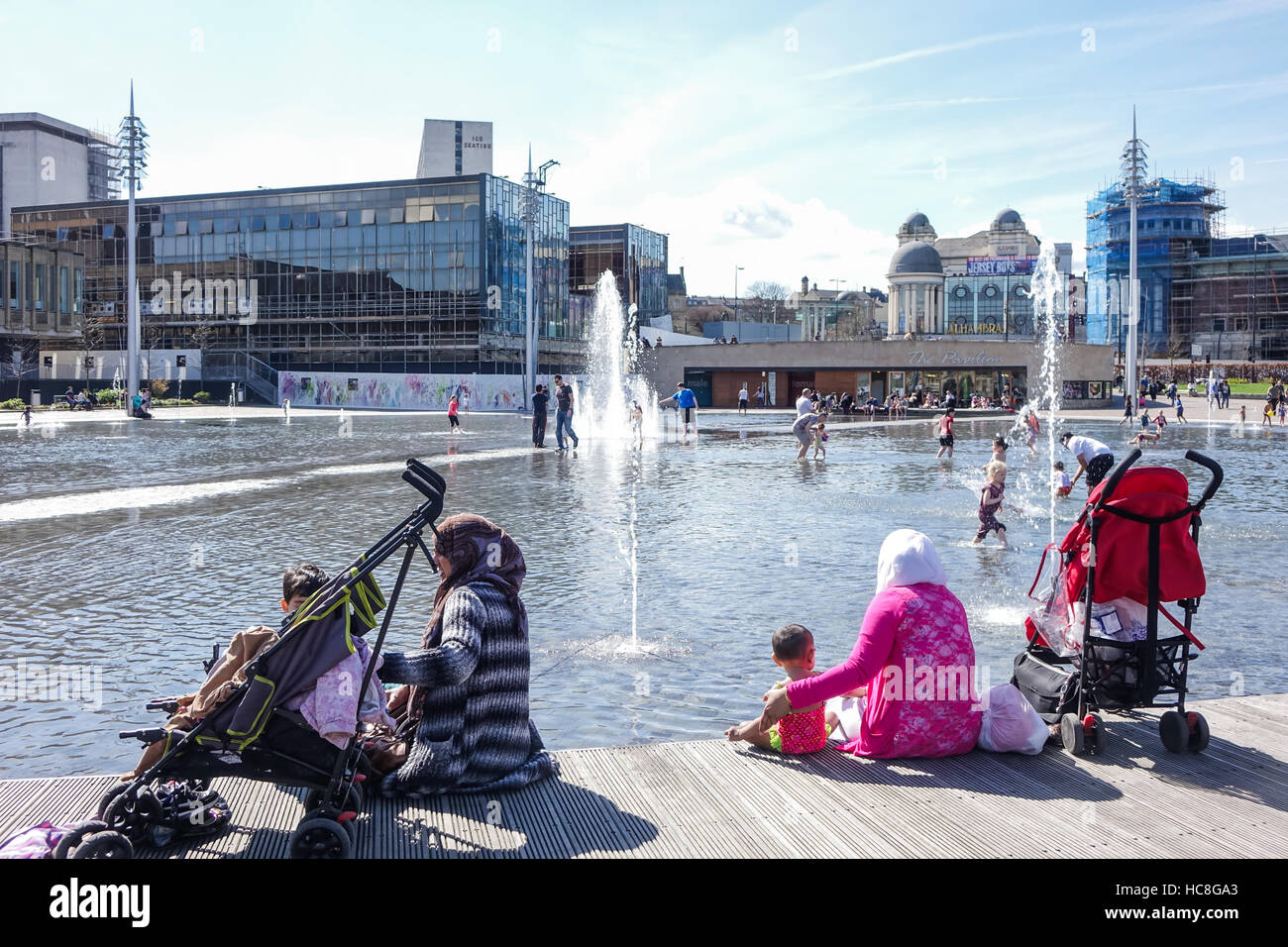 Multi ethnic scene at Bradford City Park with families having fun in the Mirror Pool - Stock Image