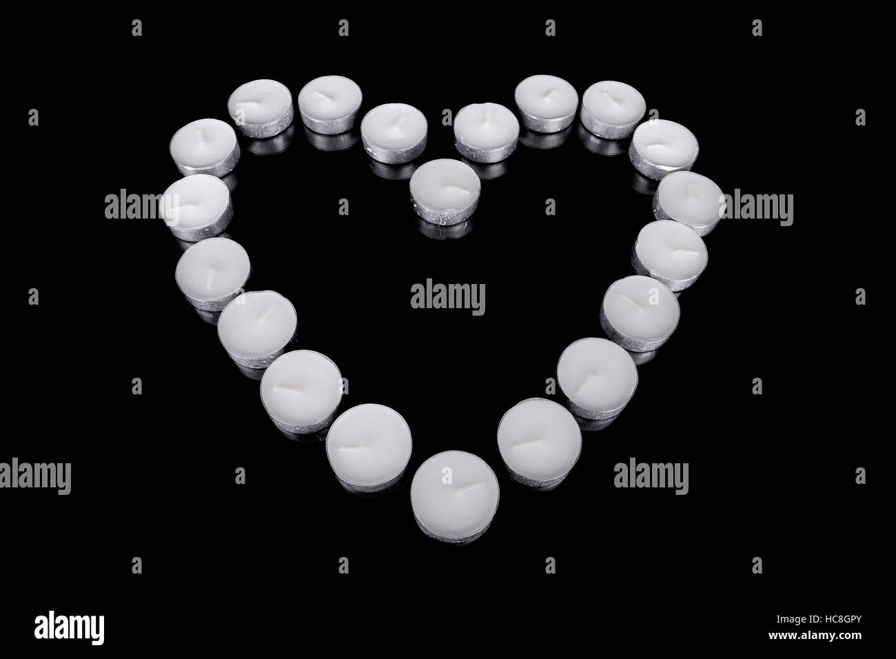 Group of white candles forming a heart  on black isolated background. Concept for St. Valentine - Stock Image