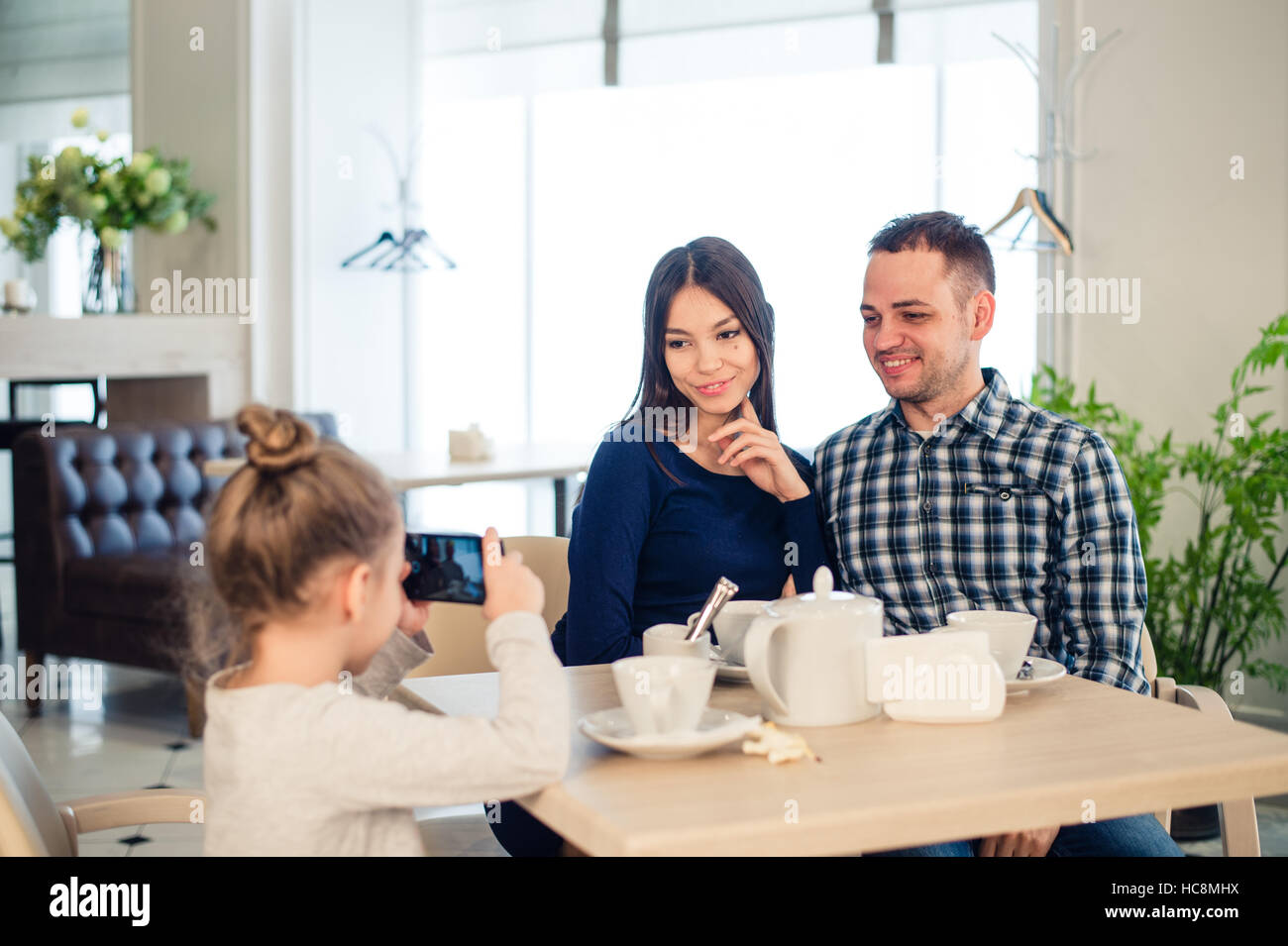 family, parenthood, technology people concept - close up of happy mother, father and little girl having dinner, - Stock Image