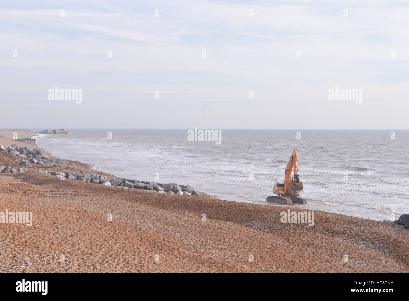 Large digger shoring up sea front by Hastings pier, Hastings UK - Stock Image