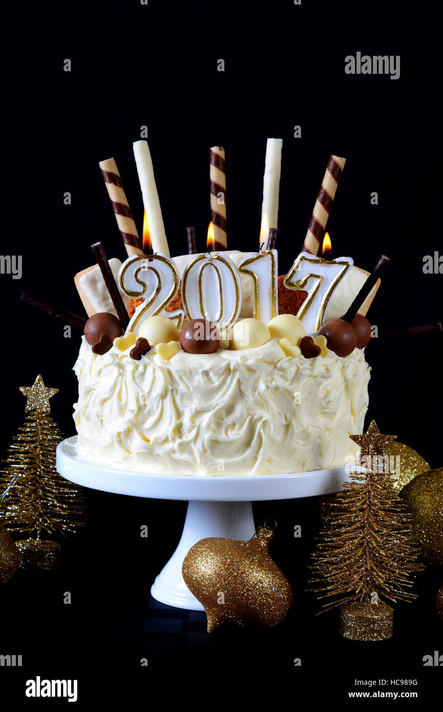 festive holidays 2017 happy new year showstopper centerpiece white chocolate cake with candy and cookies decorations against a black background
