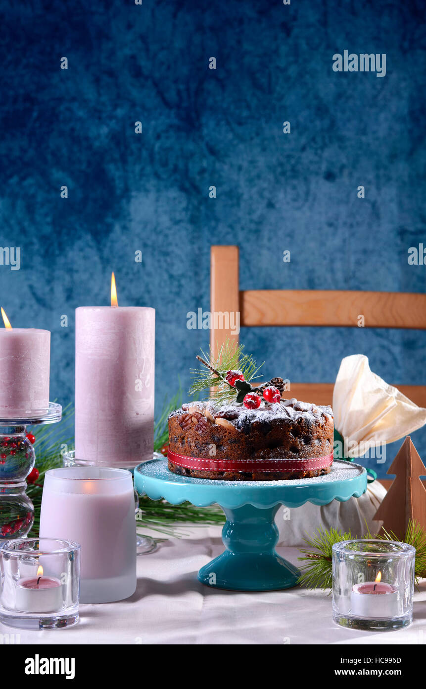 Festive holiday table with English style Christmas fruit cake with glamorous table setting with pink candles and blue background. & Festive holiday table with English style Christmas fruit cake with ...