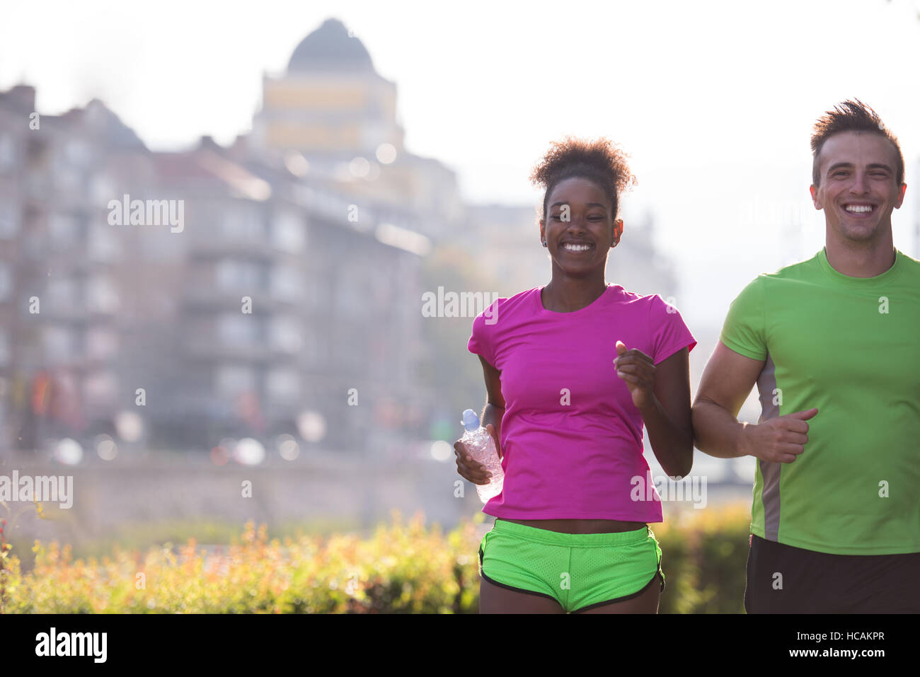 healthy young multiethnic couple jogging in the city at early morning with sunrise in background - Stock Photo