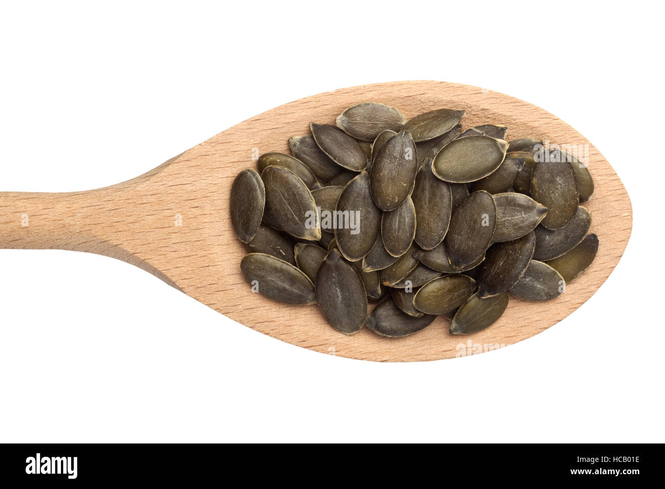 Pumpkin seeds in a wooden spoon isolated on white background - Stock Image