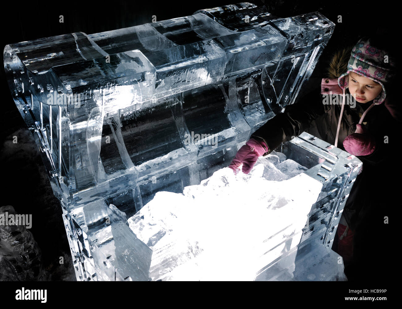 Child reaching into an illuminated treasure chest made of ice at night - Stock Image