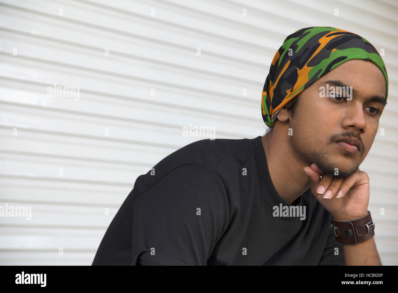Close-up of  young Indian boy with hand on chin thinking - Stock Image