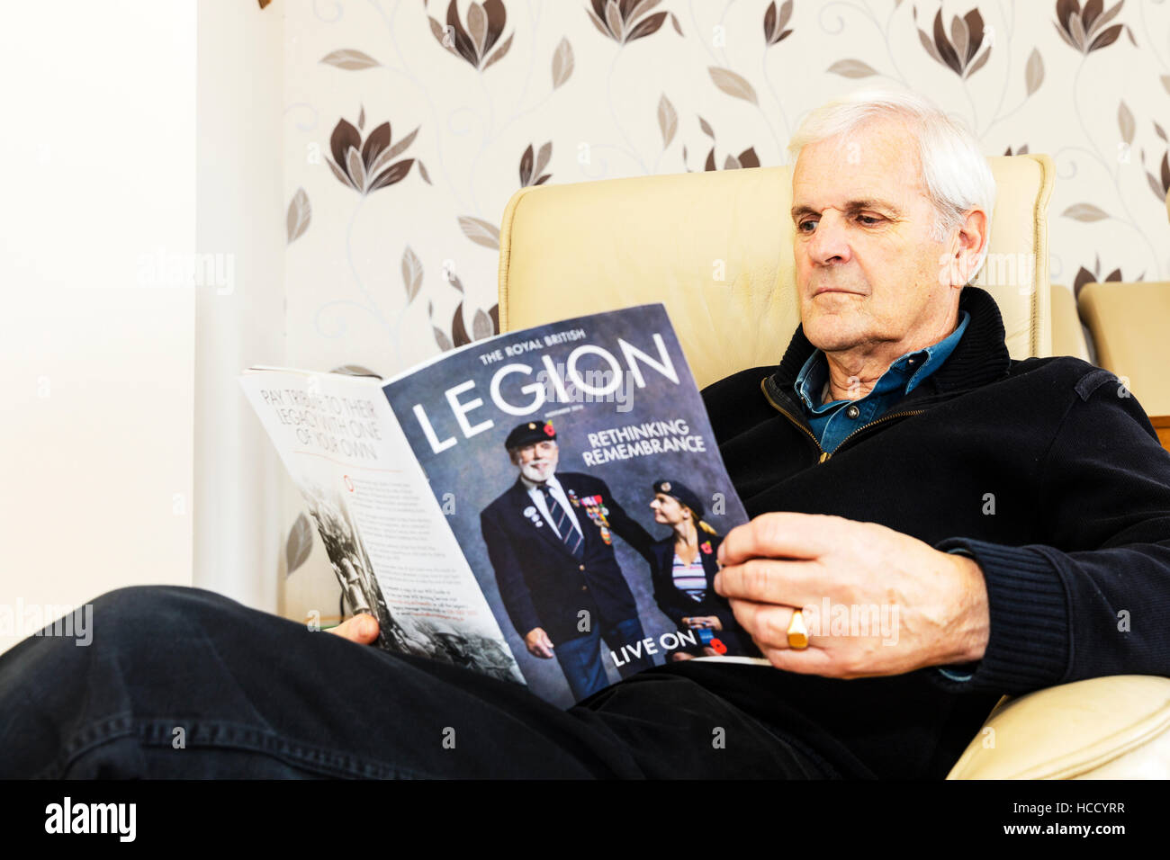 OAP reading British legion magazine man reading sat down relaxing looking at magazine at home UK England GB - Stock Image