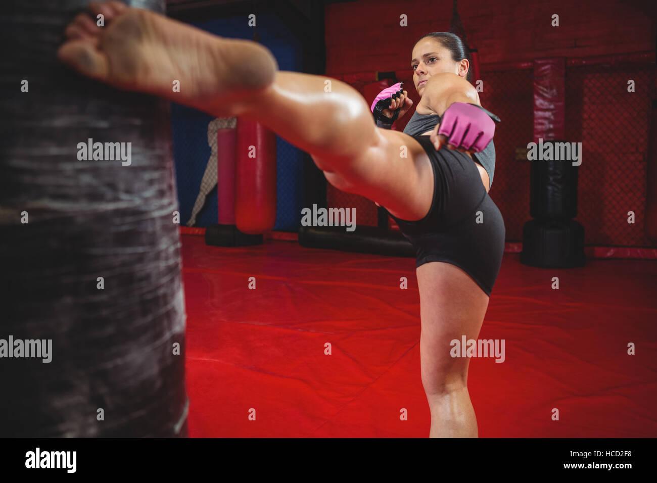 Female boxer punching a boxing bag - Stock Image