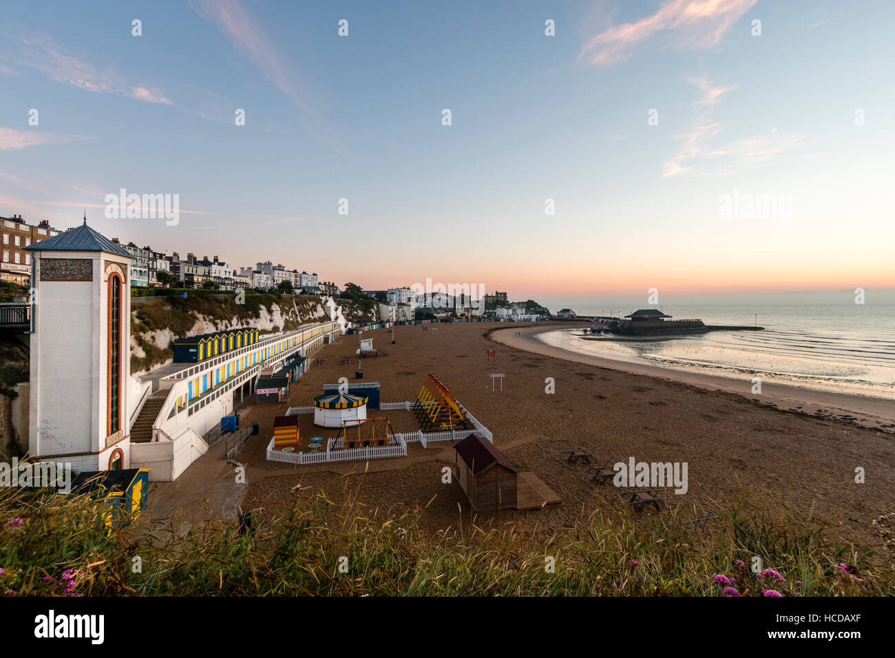 Broadstairs seafront, lift-shaft, cliffs, beach huts and seafront buildings with beach, sea and harbour during the - Stock Image