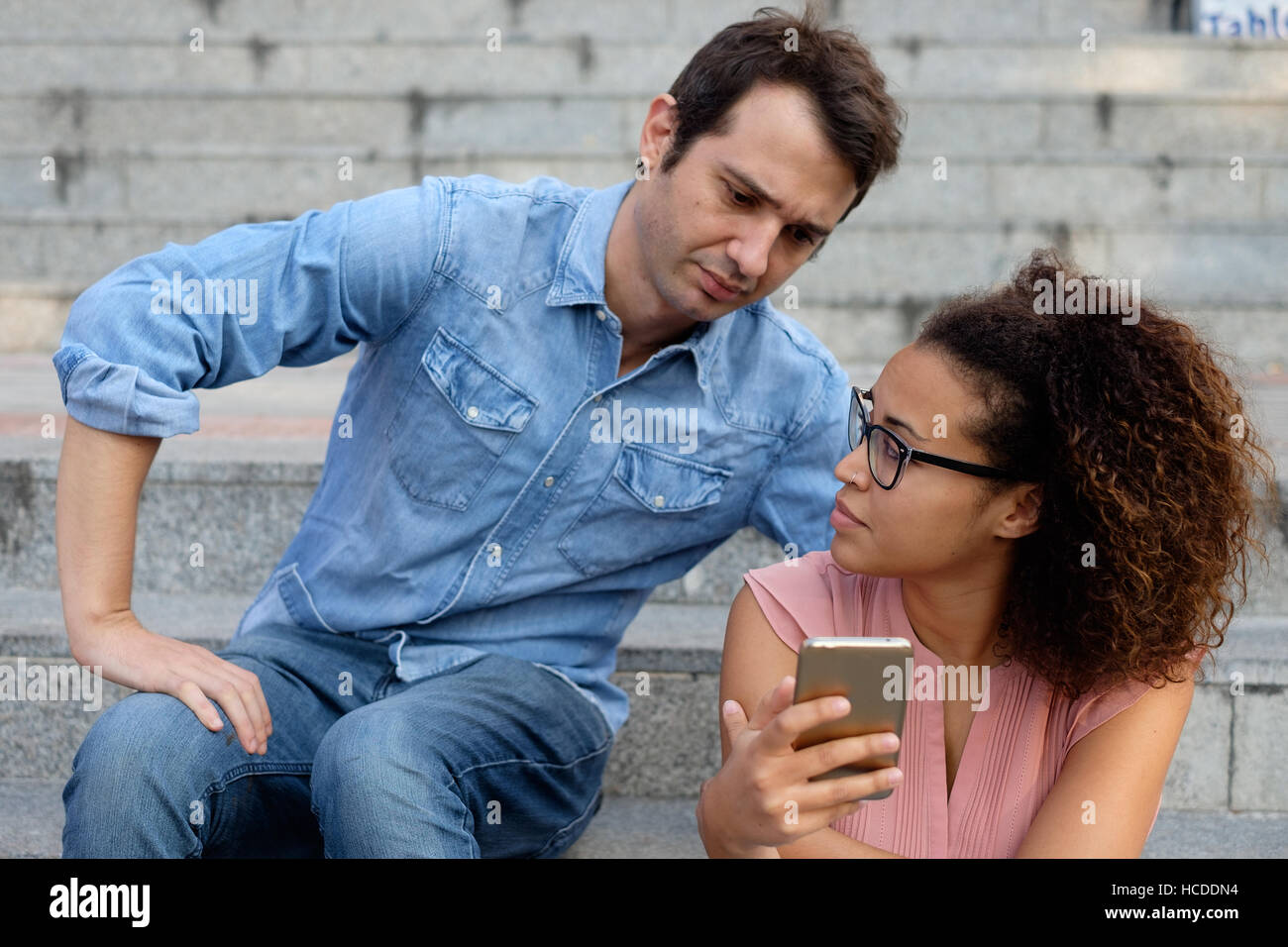 Man spying the mobile phone of her girlfriend - Stock Image