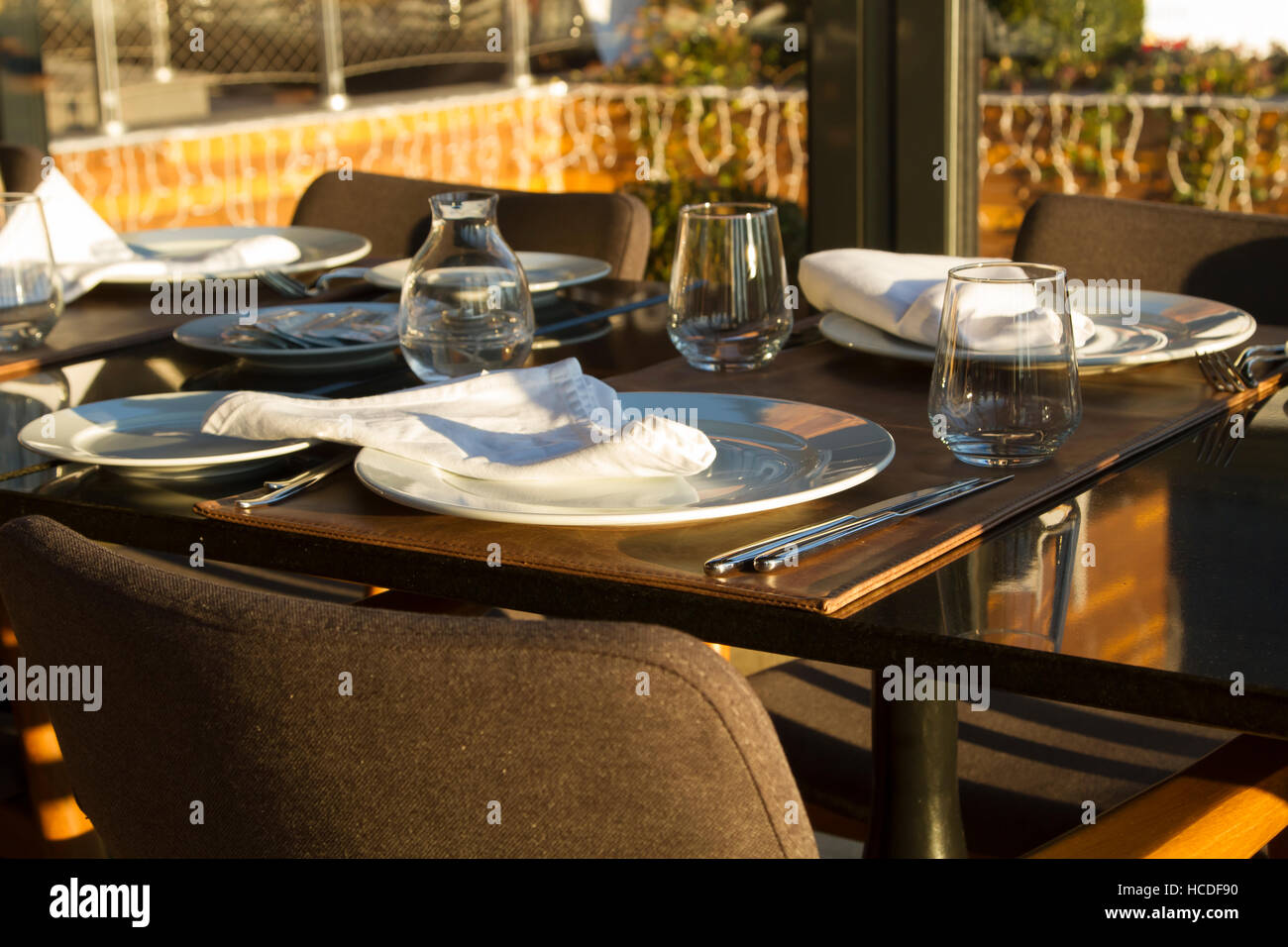 Table in the restaurant served for several persons with glasses, plates - Stock Image