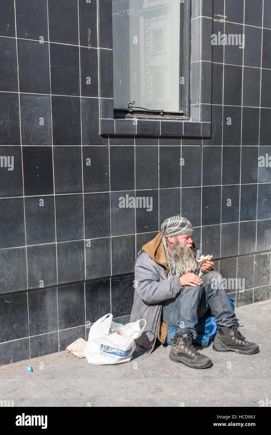 London, England, UK, 21 April 2016. A homeless man sitting underneath a window eating a sandwich. - Stock Image