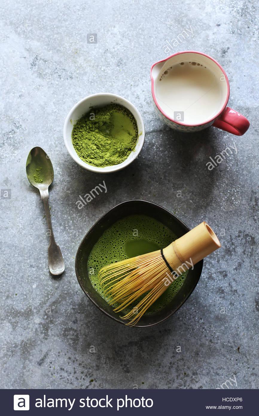 Preparing matcha latte.Green tea powder in a bowl and coconut milk in a mug.Top view - Stock Image