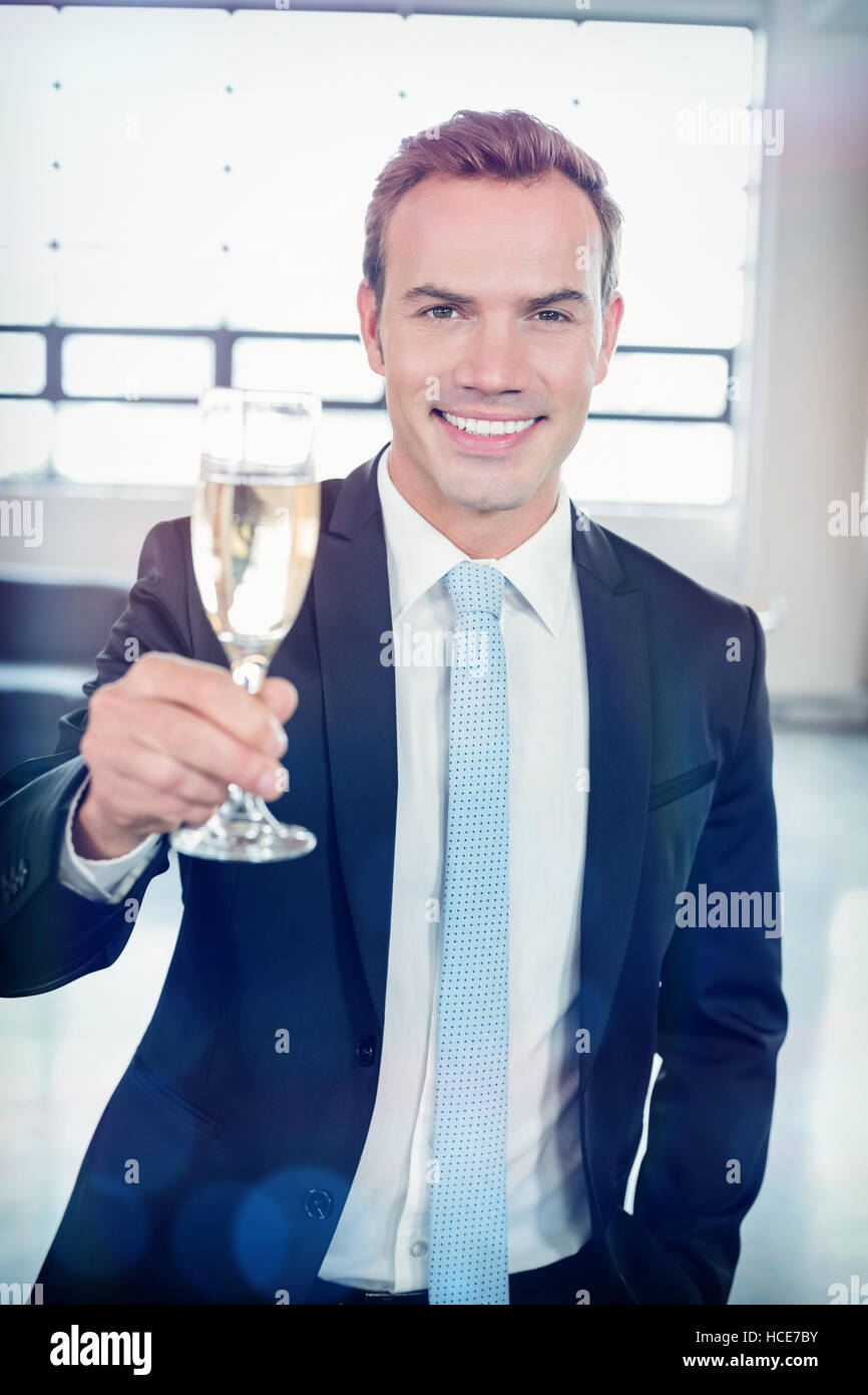 Portrait of businessman holding champagne flute - Stock Image