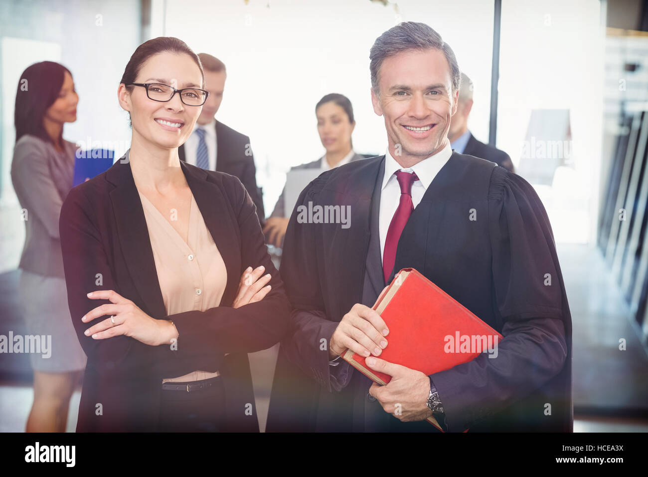 Portrait of businesswoman standing with lawyer - Stock Image