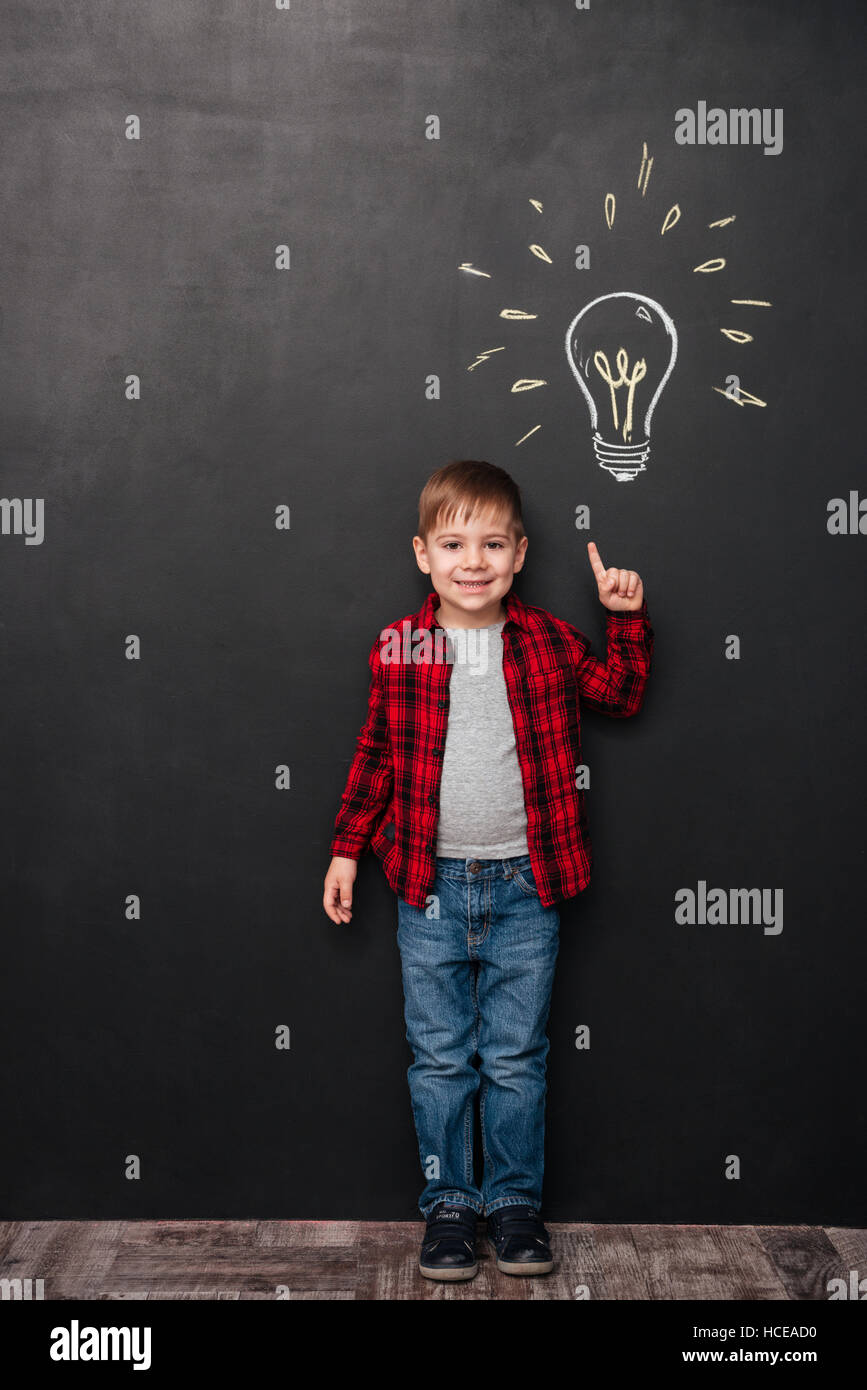 Picture of little boy pointing up and having an idea over chalkboard background with drawings. Looking at camera. - Stock Image