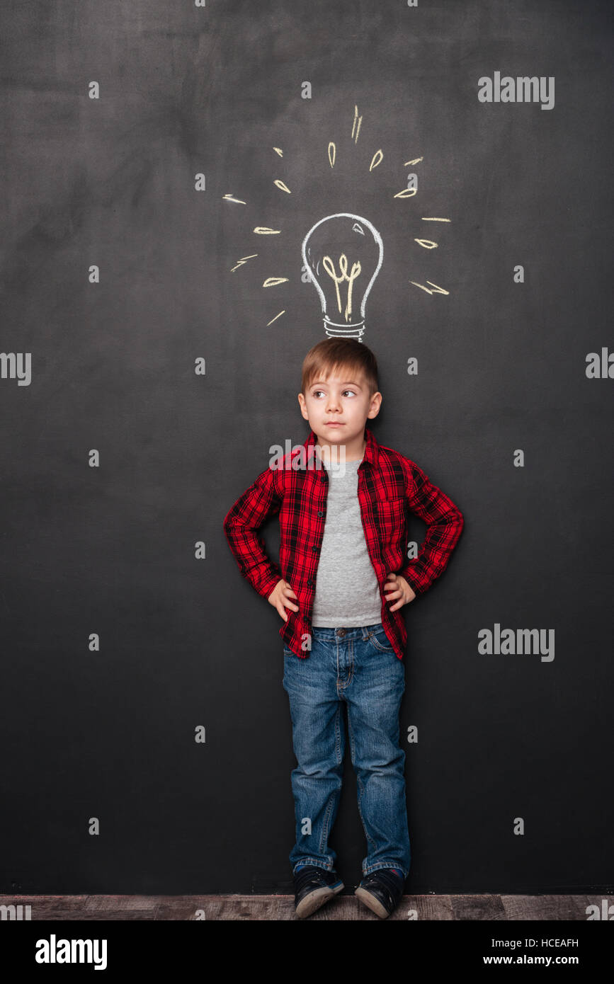 Photo of a little cute boy having an idea over chalkboard background with drawings. Look aside. - Stock Image