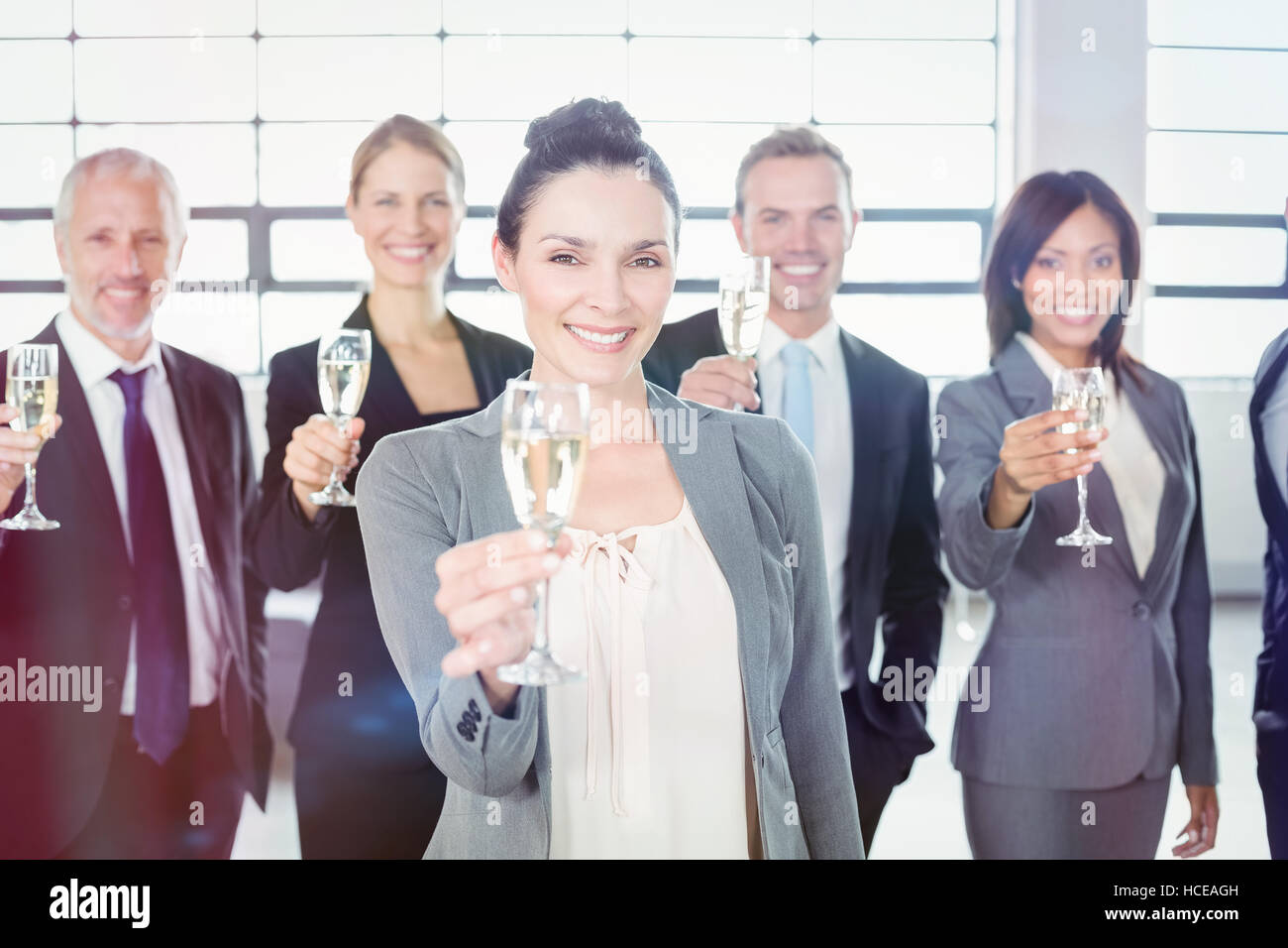 Portrait of business team holding champagne flute - Stock Image