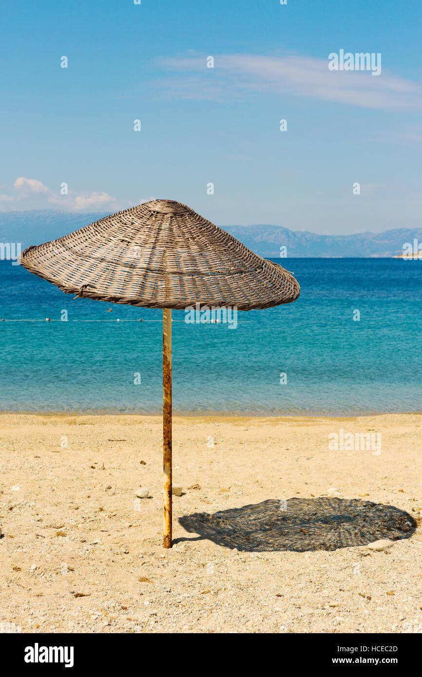 Straw umbrella in a sandy beaches of Kusadasi Region in Aegean Sea coastline of Turkey - Stock Image