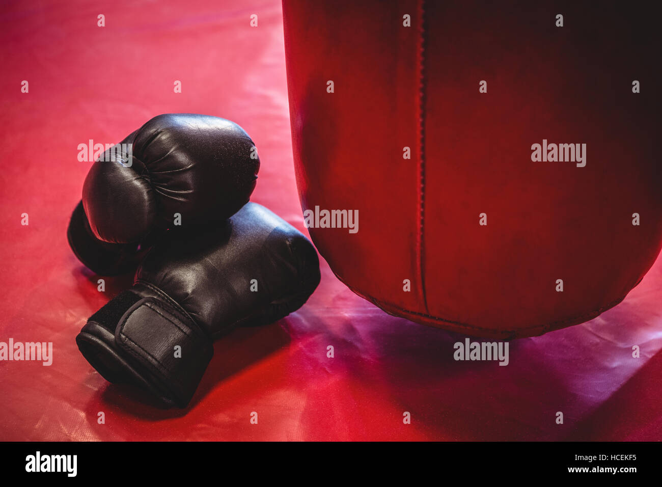 Boxing gloves and punching bag on red surface - Stock Image