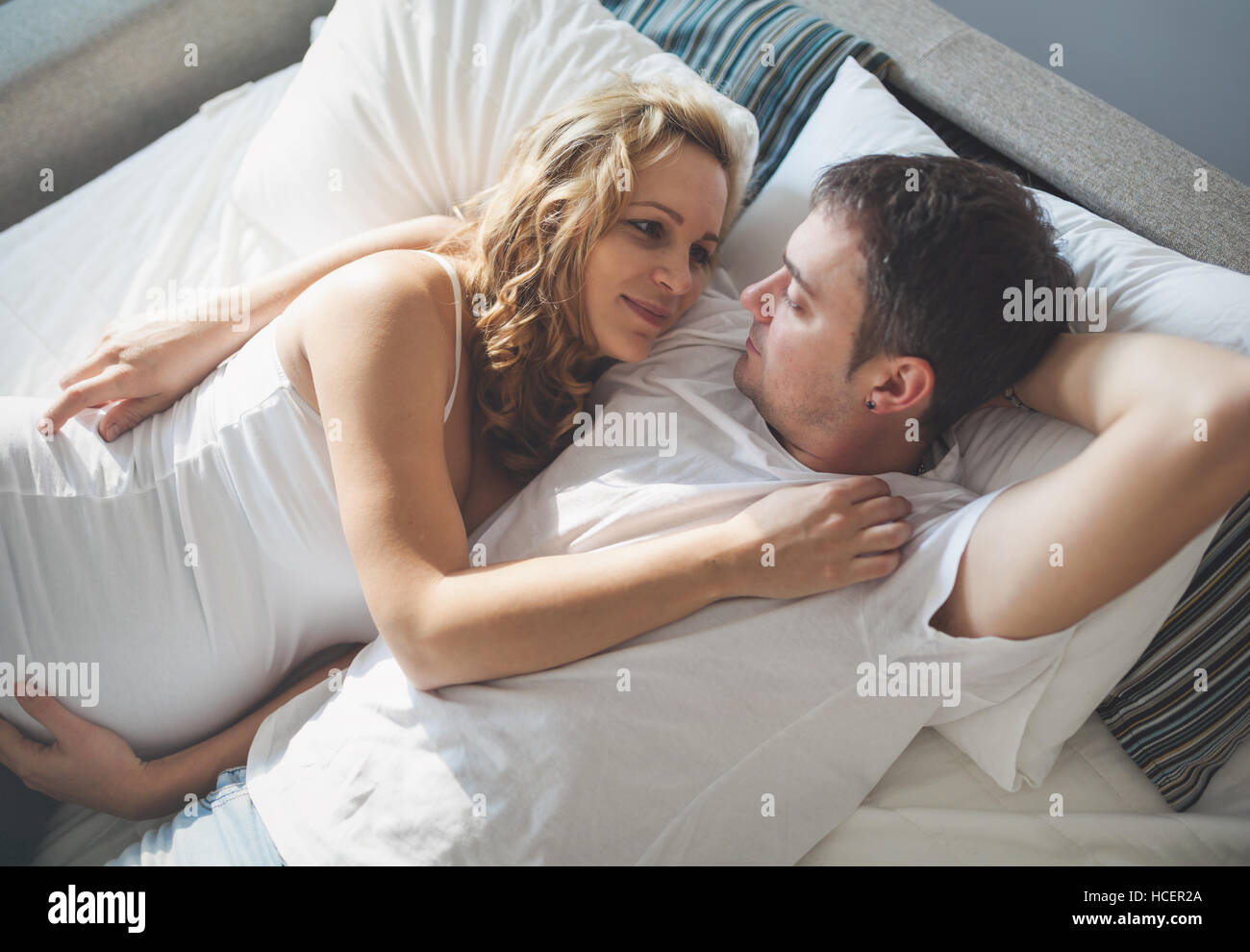 . Pregnant happy wife lying in bed with husband Stock Photo  128173874