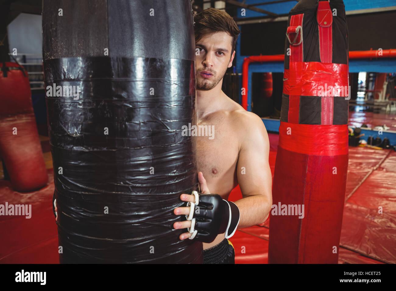 Boxer holding a punching bag - Stock Image