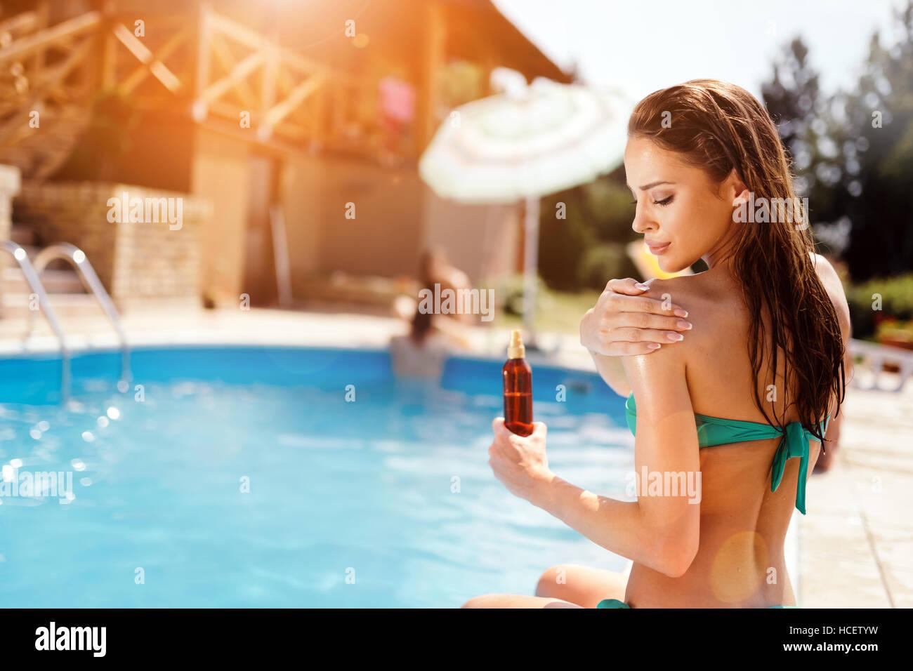 Woman applying sun uv protection lotion - Stock Image