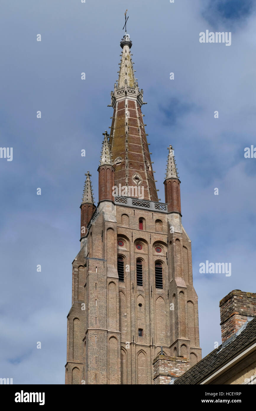 Onze-Lieve-Vrouwekerk, or Church of Our Lady, Bruges, Belgium. Red brick spire on brown brick tower, with stone - Stock Image