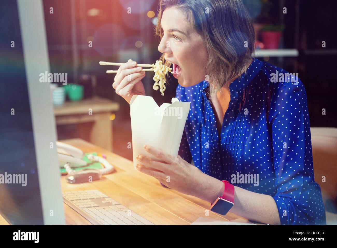 Businesswoman eating noodles at desk - Stock Image