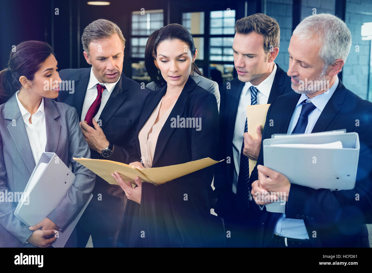 Lawyer looking at documents and interacting with businesspeople - Stock Image