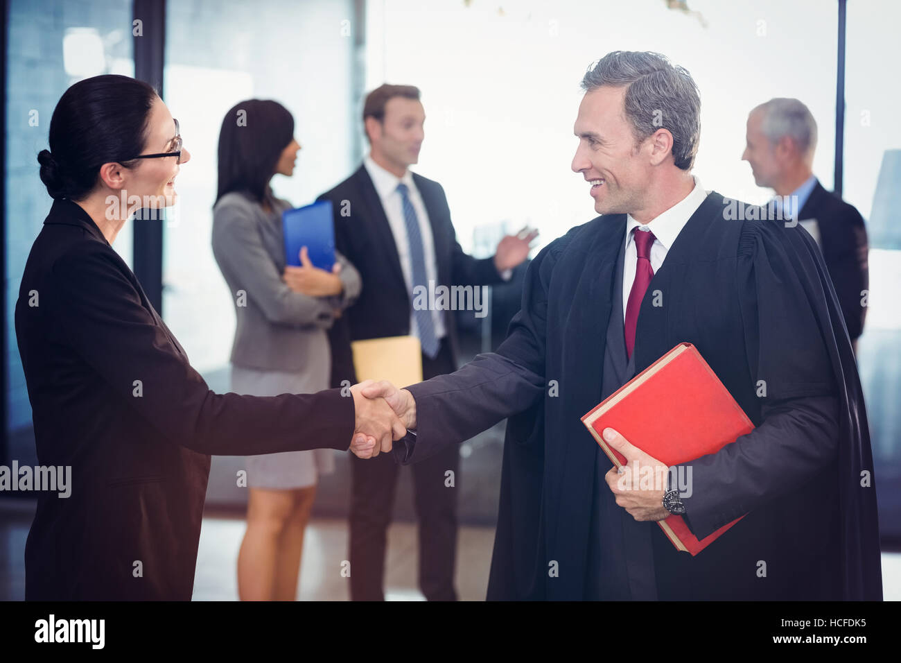 Businesswoman shaking hands with lawyer - Stock Image