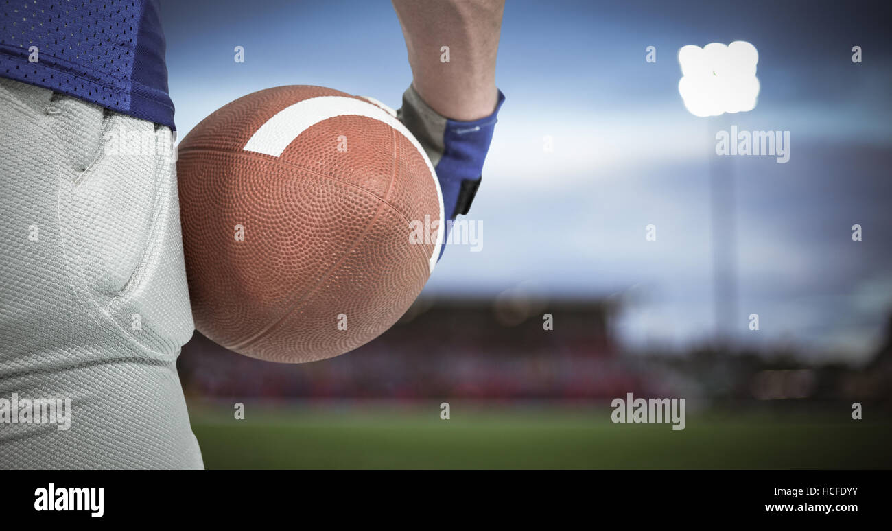 Composite image of american football player holding ball - Stock Image