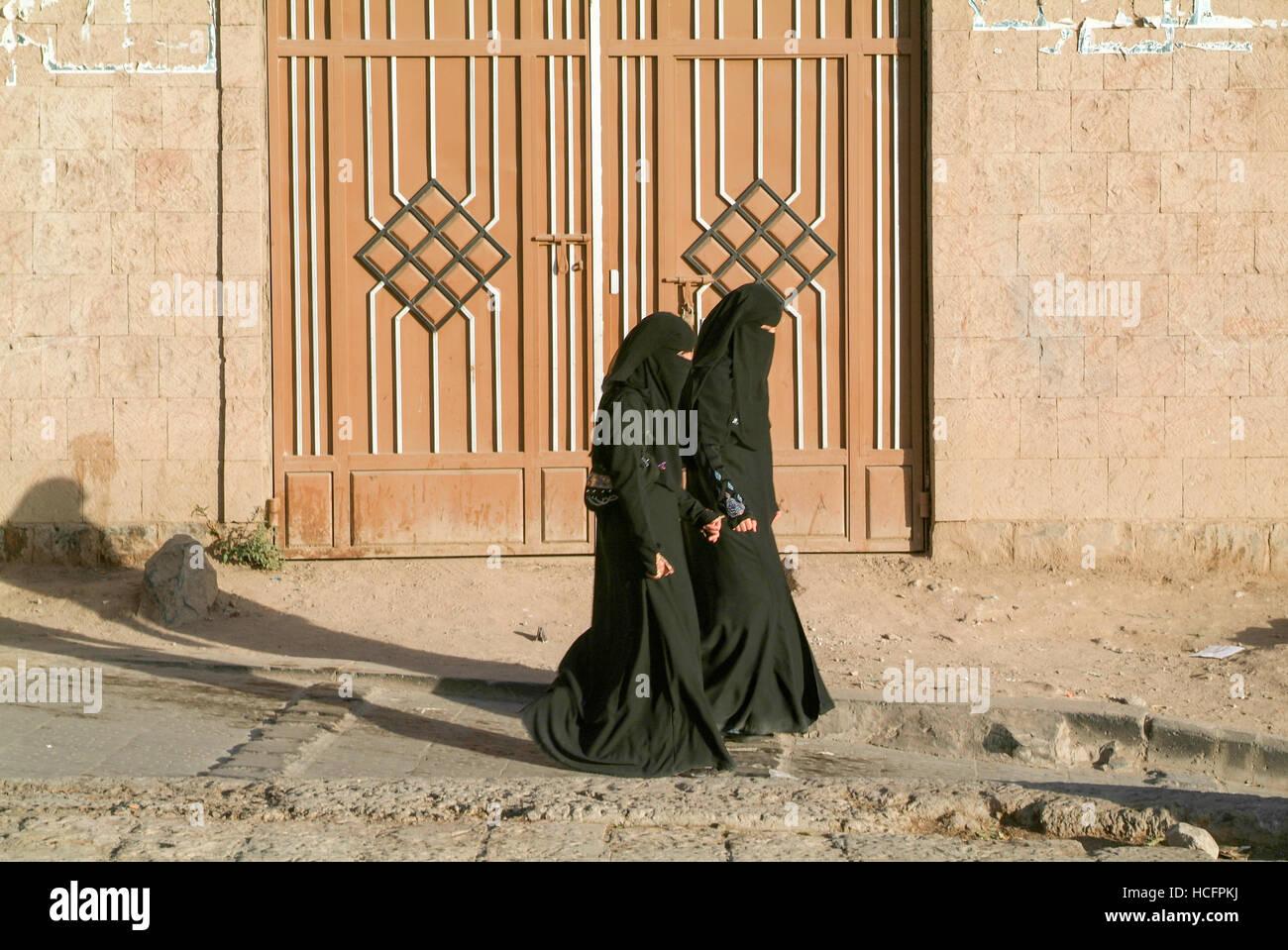 Sana, Yemen - 3 January 2008: women wearing the burqa and walking on the street of old Sana, Yemen - Stock Image