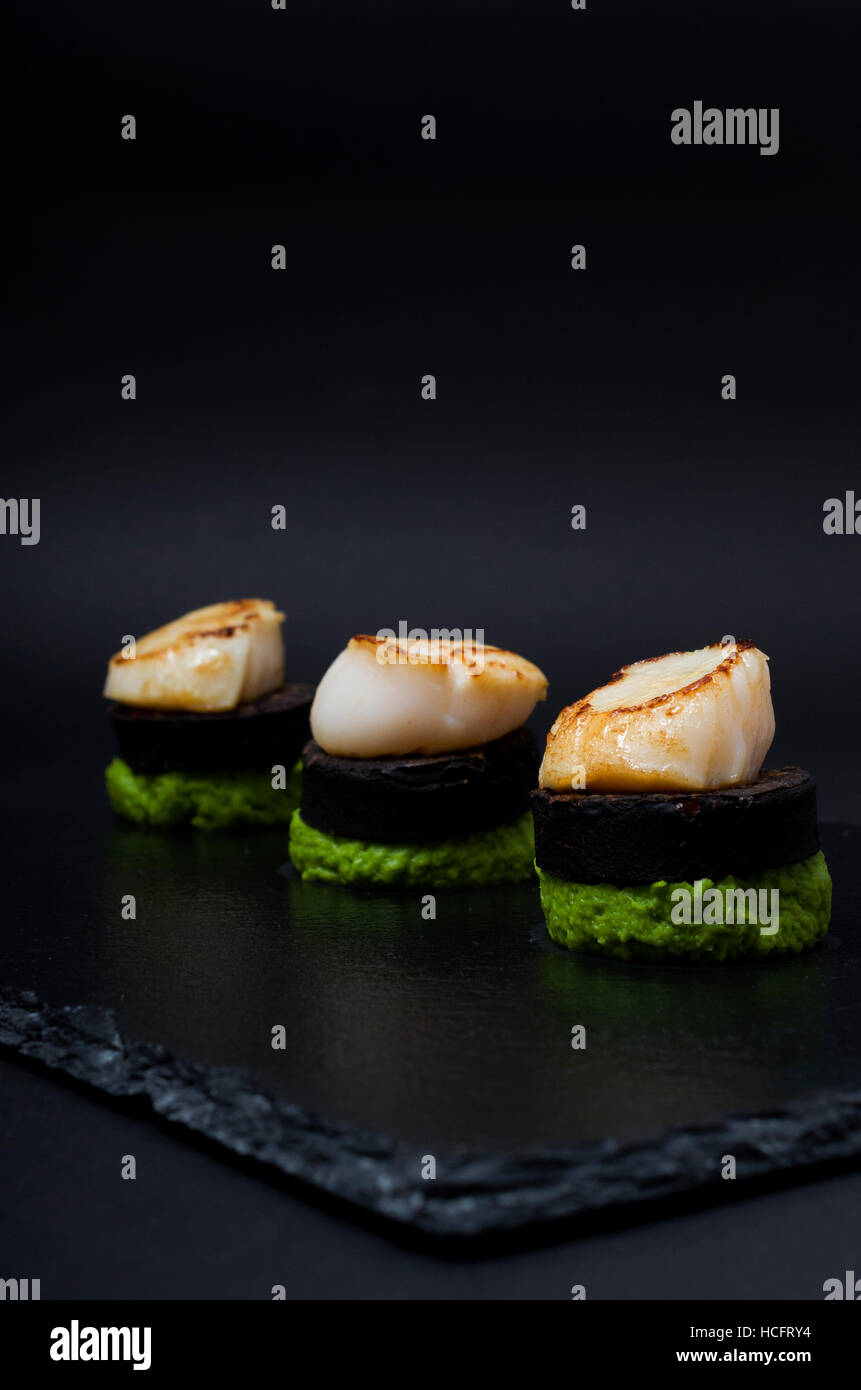 Pan-fried scallops served with black pudding and crushed pea puree served upon slate - Stock Image