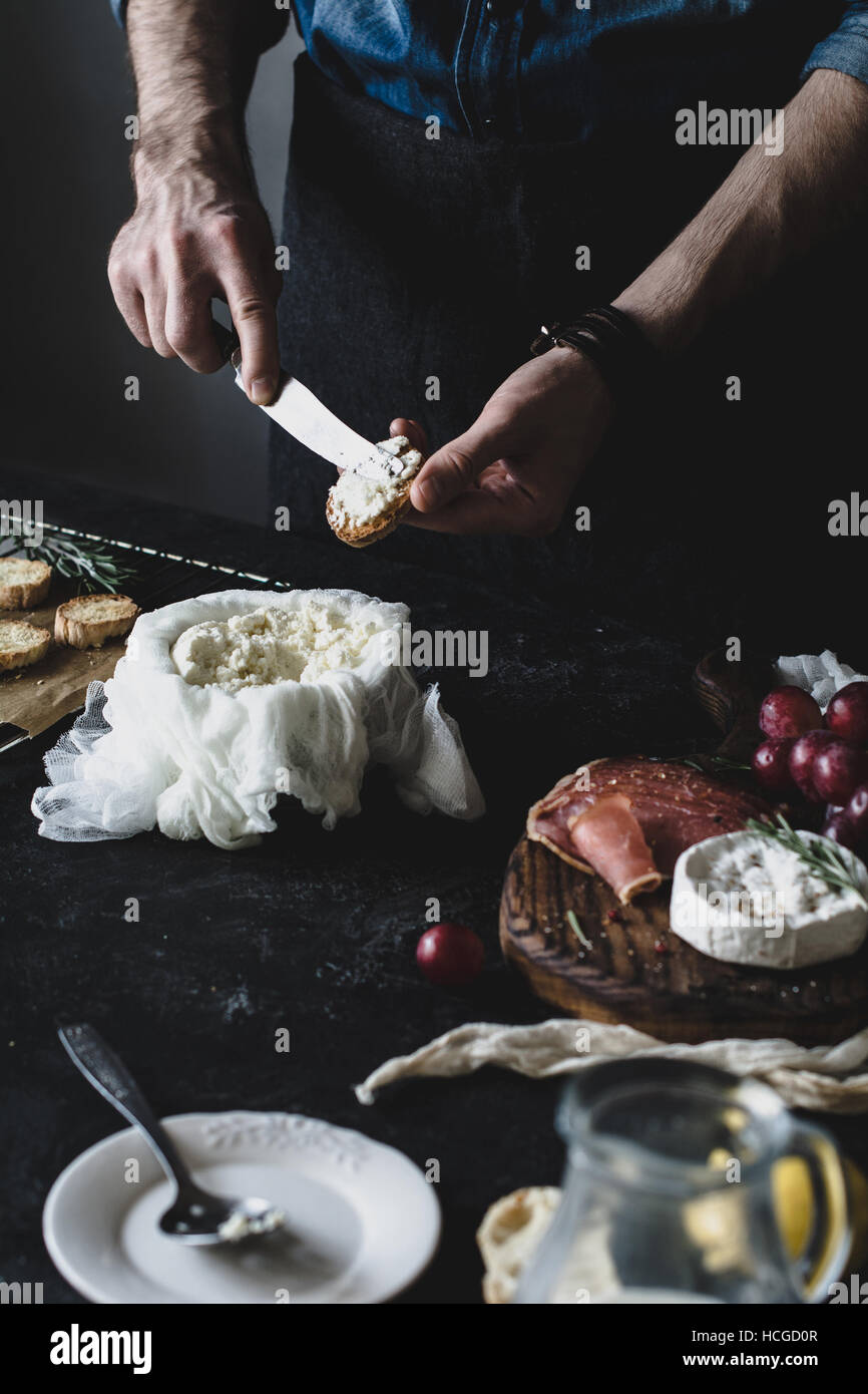 Chef prepares crostini with fresh cheese for a wine dinner or party. Selective focus, desaturated effect, toned Stock Photo