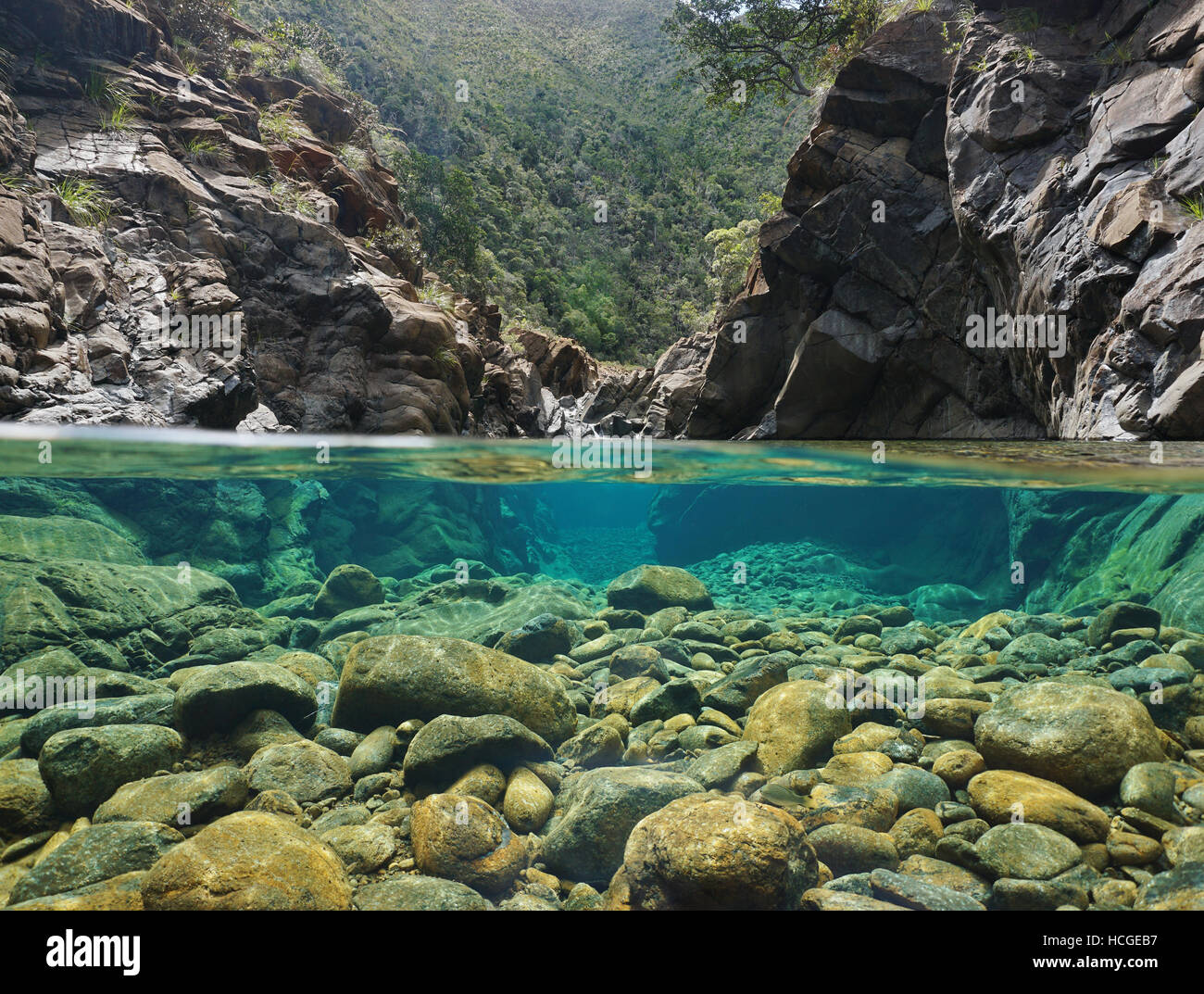 Rocks over and under the water split by waterline in a river with clear water, Dumbea river, New Caledonia Stock Photo