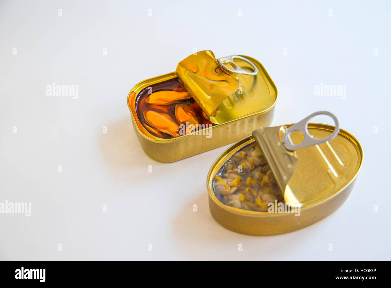 Tins of marinade mussels and common cockles. - Stock Image