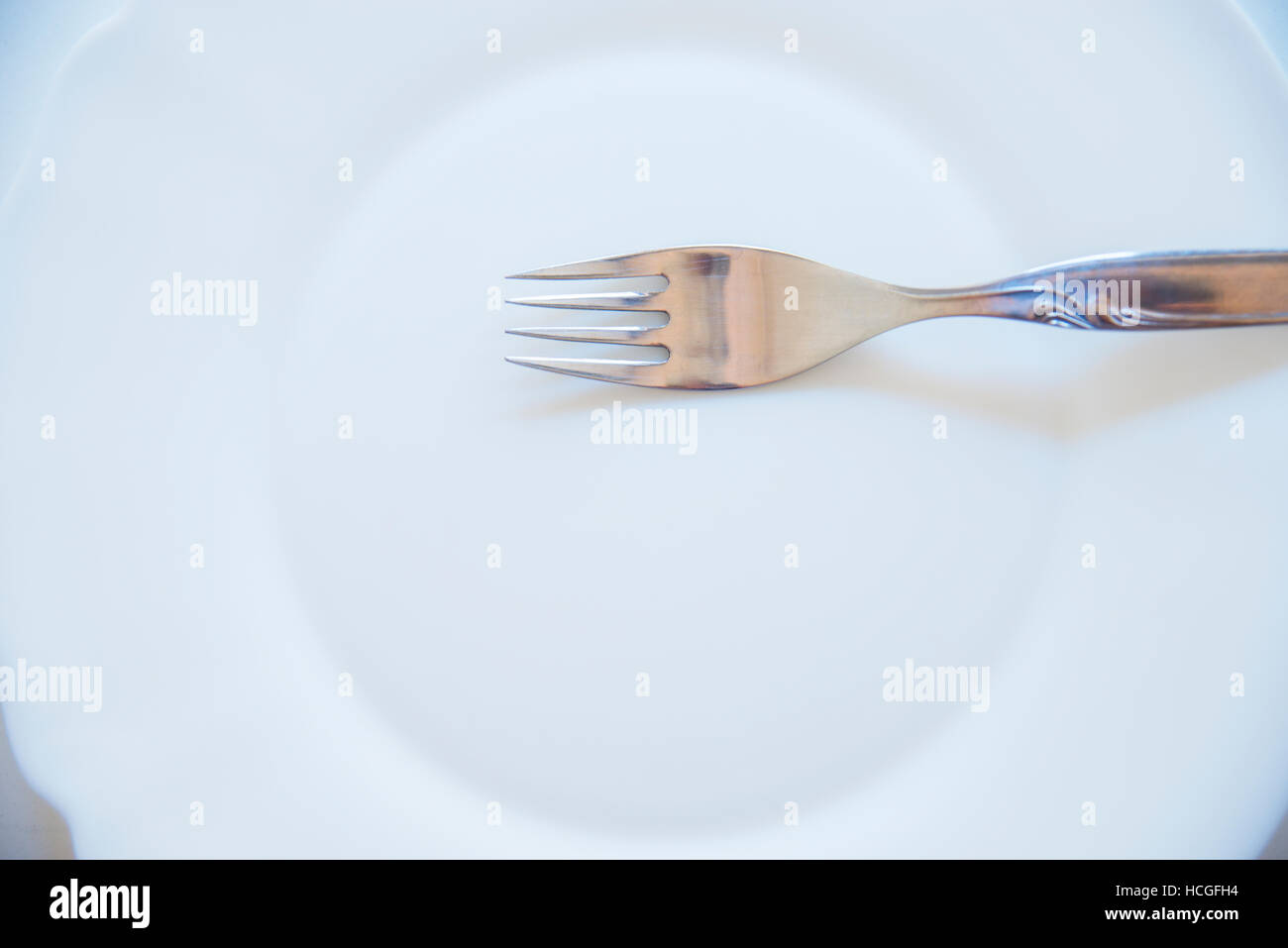Fork on empty dish. - Stock Image