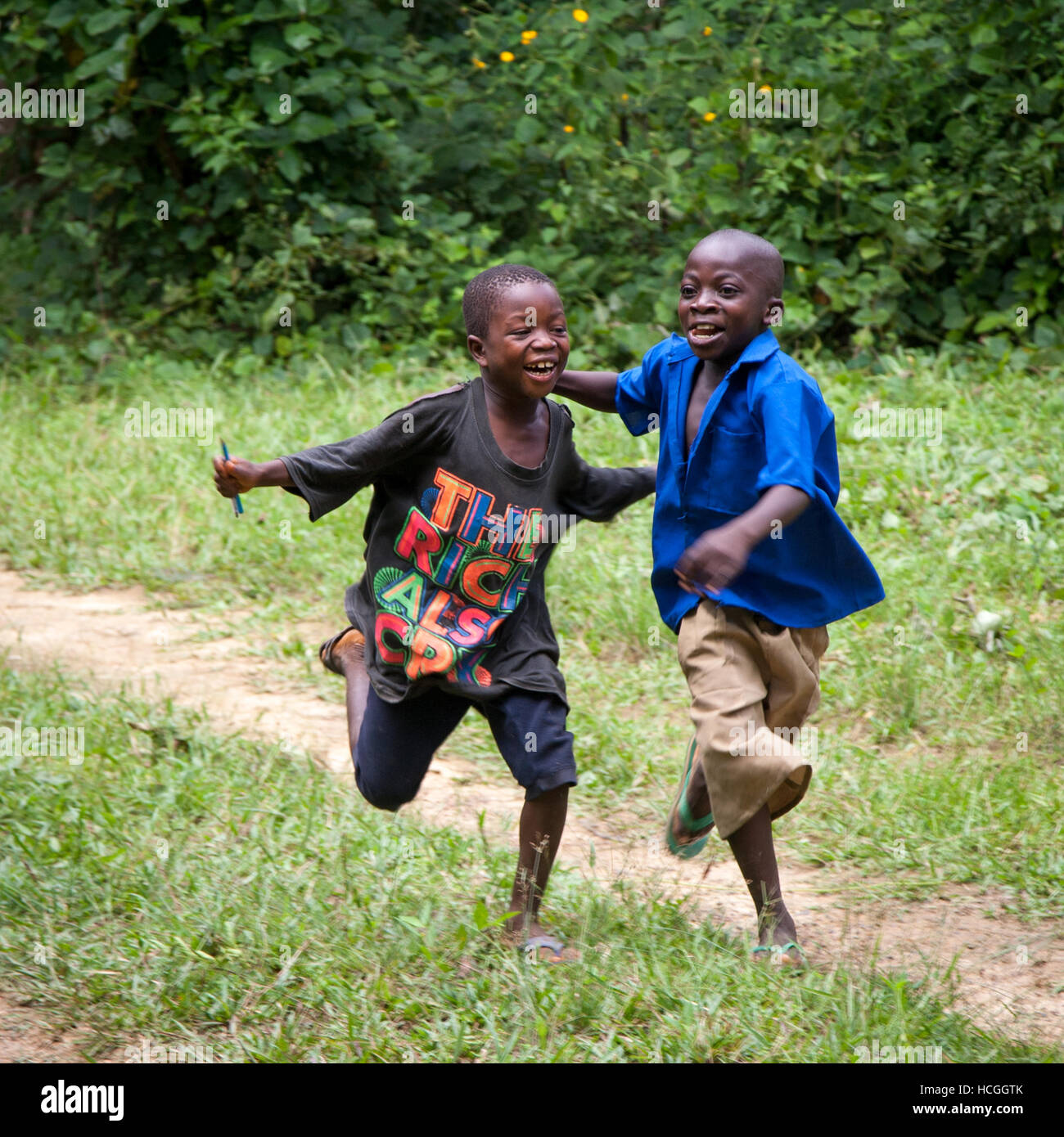 """Two boys from Sierra Leone are happy, running through their rural village. The t-shirt spells: """"The Rich also cry"""" Stock Photo"""