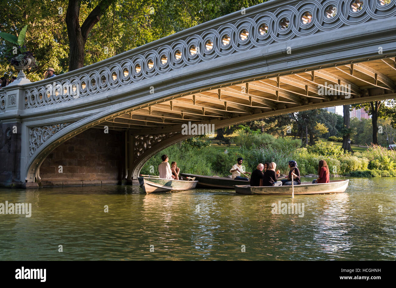 People boating in rowing boats in Summer on The Lake under Bow Bridge in Central Park, New York City. - Stock Image